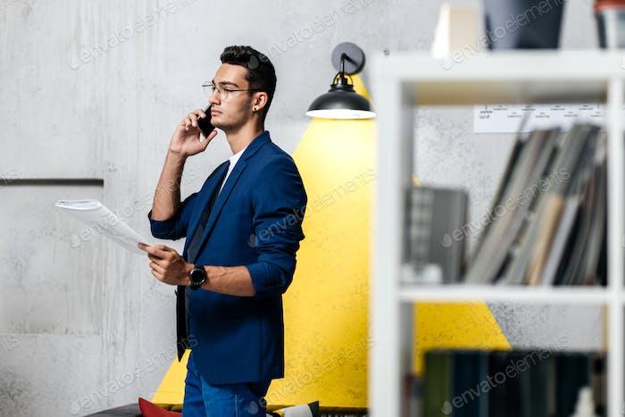 Arquitecto profesional hablando por teléfono en una habitación con un interior elegante con sofá con almohadas