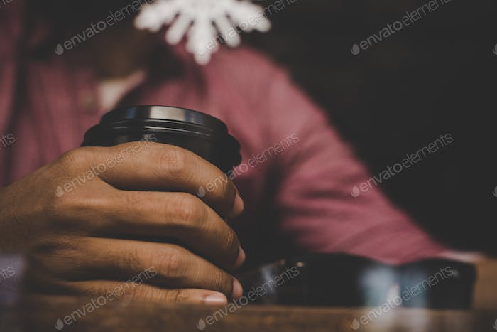 Hipster man holding a cup of coffee and sitting on cafe bar. Vintage color style.