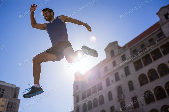 Handsome athlete leaping in front of building in the city