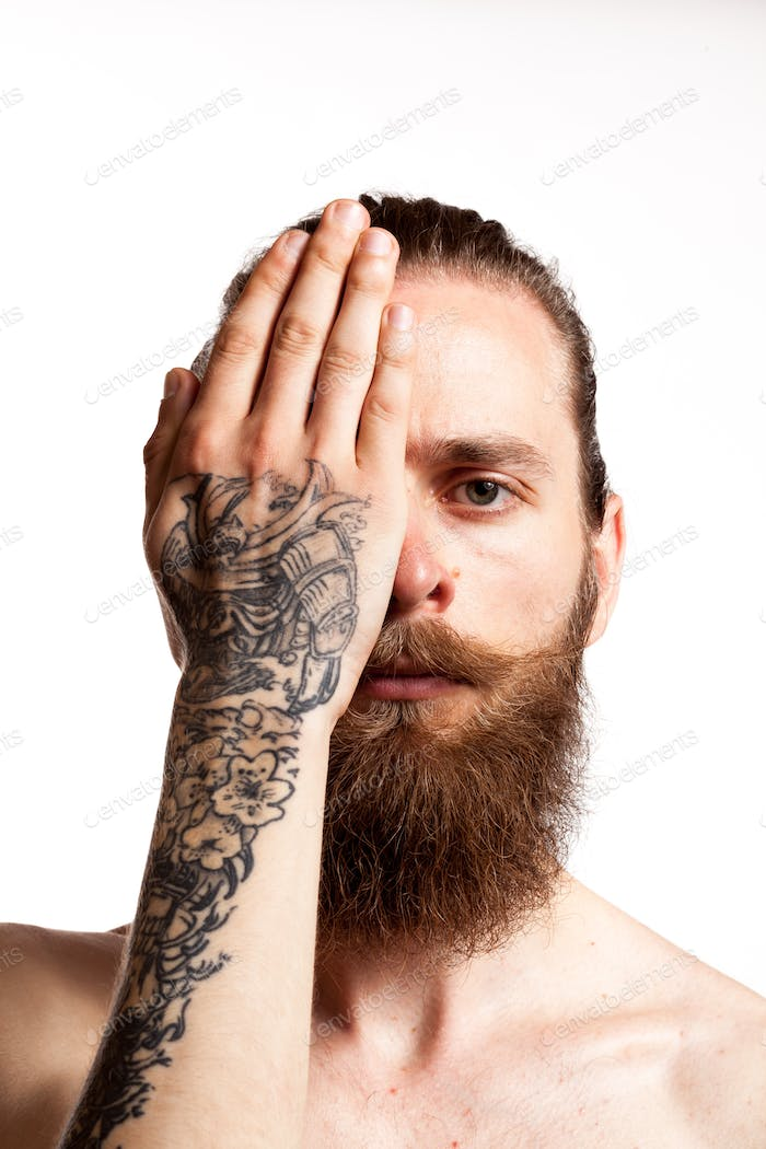 Cool hipster with long beard and tattoes over white background