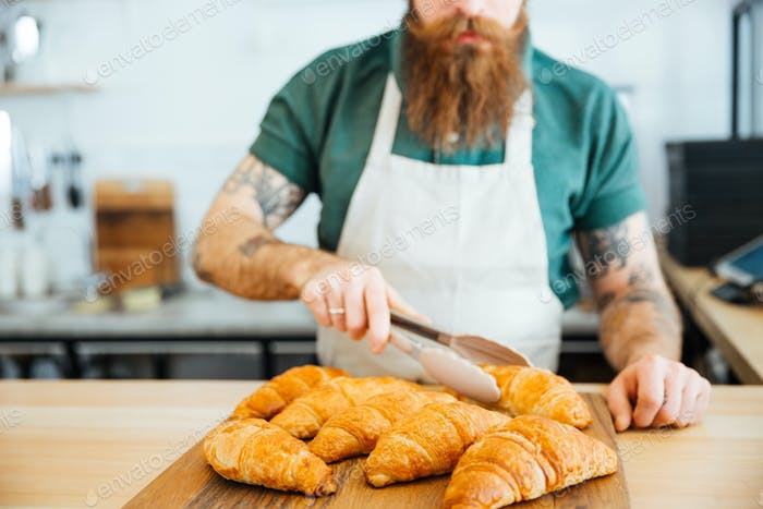 Young man barista with beard taking croissant using tongs
