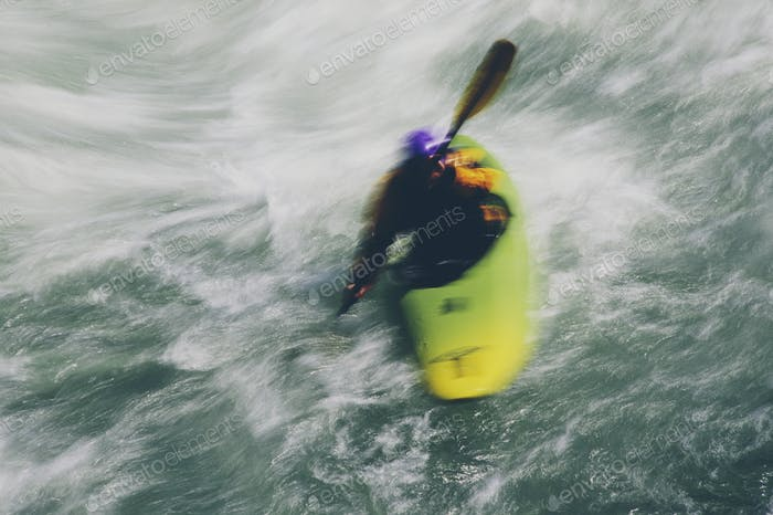 Whitewater kayaker paddles and surds large river rapids on a fast flowing river
