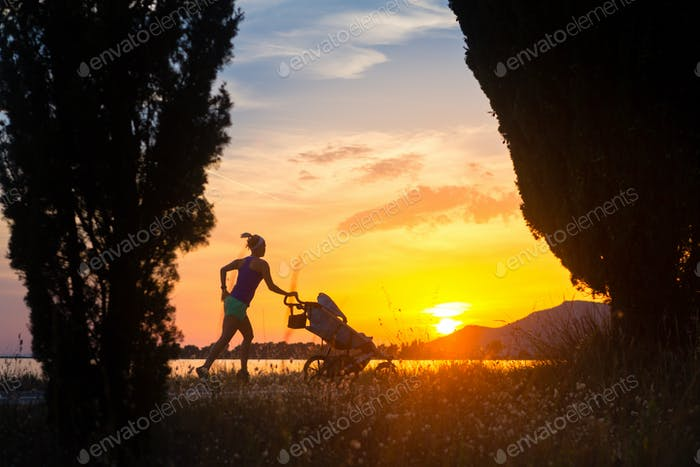 Silhouette of running mother with stroller enjoying motherhood a