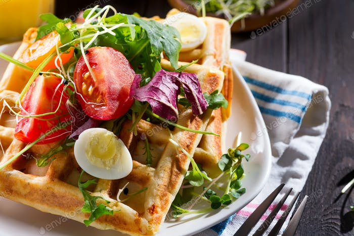 Close up view of freshly cooked healthy breakfast with homemade waffles, tomatoes and cut egg on a