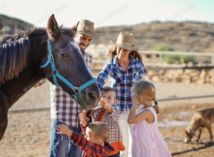 Familia feliz abrazo caballo al aire libre ar rancho - Amor humano y animal