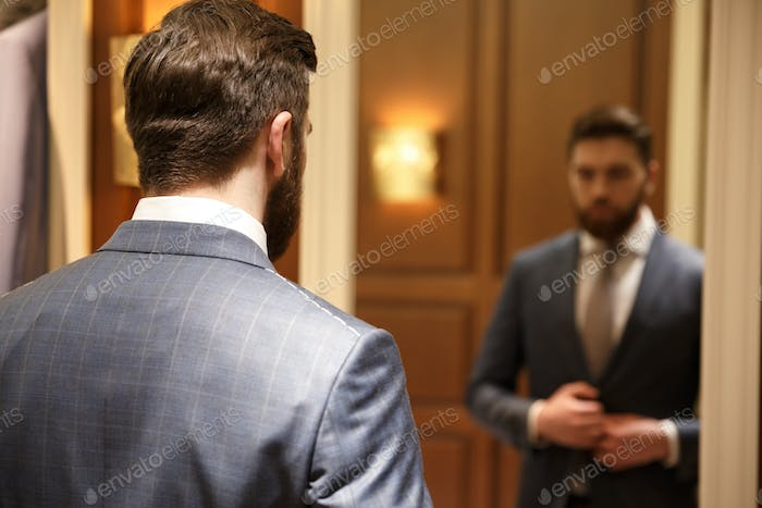 View from back of bearded man looking at the mirror