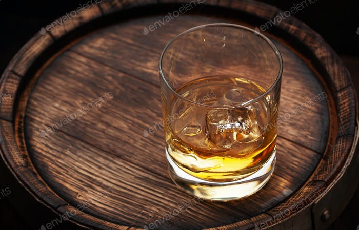 Scotch whiskey glass and old barrel