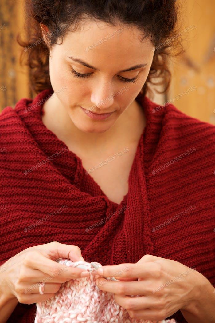 Close up beautiful young woman knitting sweater