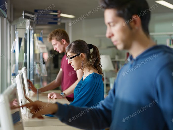 Group Of College Students Using Pc Computer In Library