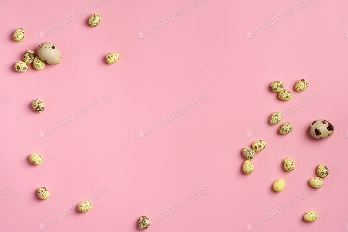 Natural organic quail eggs different size on a pastel pink background. Flat lay