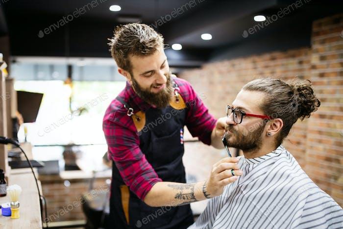 Friseur Rasieren einen bärtigen Mann in einem Friseurladen, Nahaufnahme