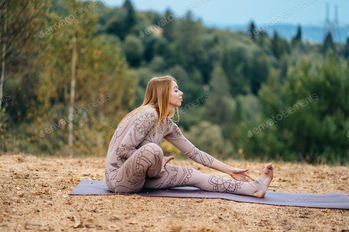Eine Frau praktiziert Yoga am Morgen in einem Park an einer frischen Luft