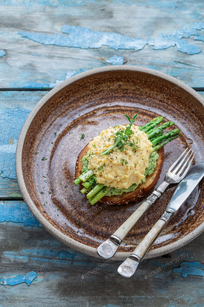 Scrambled egg with asparagus and avocado on toast, copy space