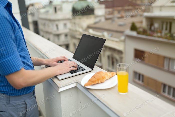 Деловой человек, использующий ноутбук на крыше