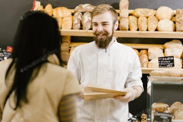 Харизматичный пекарь с бородкой и усами дает клиенту бумажный мешок хлеба в пекарне