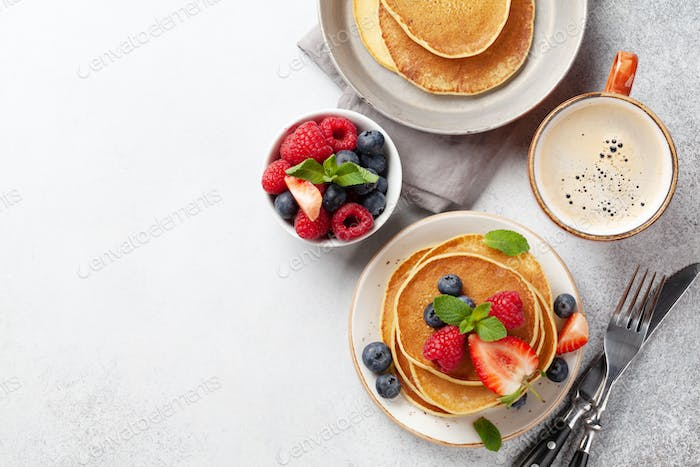Delicious pancakes with berries and coffee