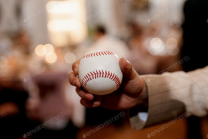 baseball ball with red stitching in the hand