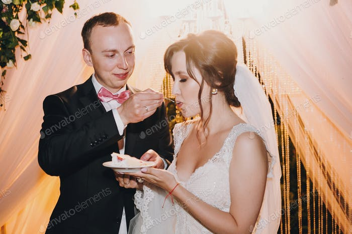 Gorgeous bride and stylish groom tasting delicious wedding cake