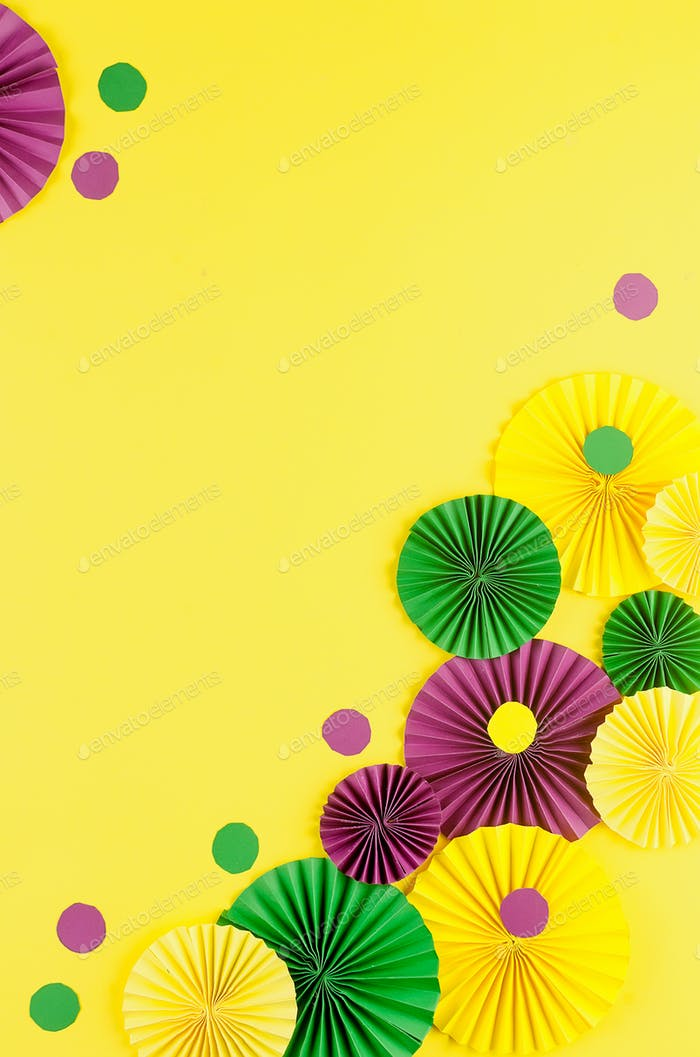 Colorful paper confetti, carnivale mask and colored serpentine on a yellow background, carnival