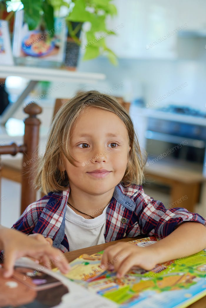 Joyful boy with books sits at table and looks away in room