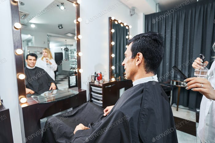 Hairdresser bringing spray bottle and comb to customer from behind
