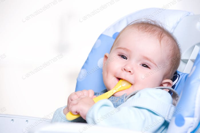 Happy baby with spoon