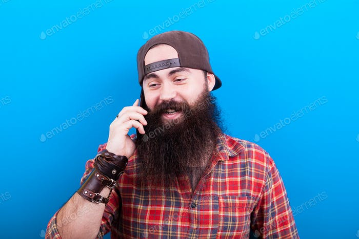 Happy man with long beard talking on the phone