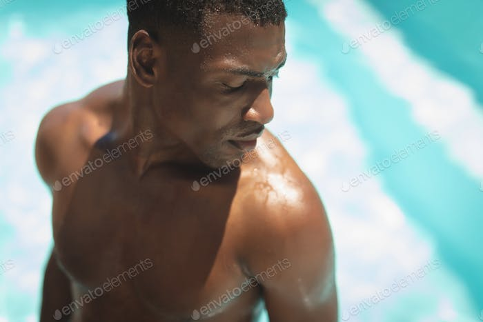 Close-up of young African American man at poolside in his backyard on a sunny day