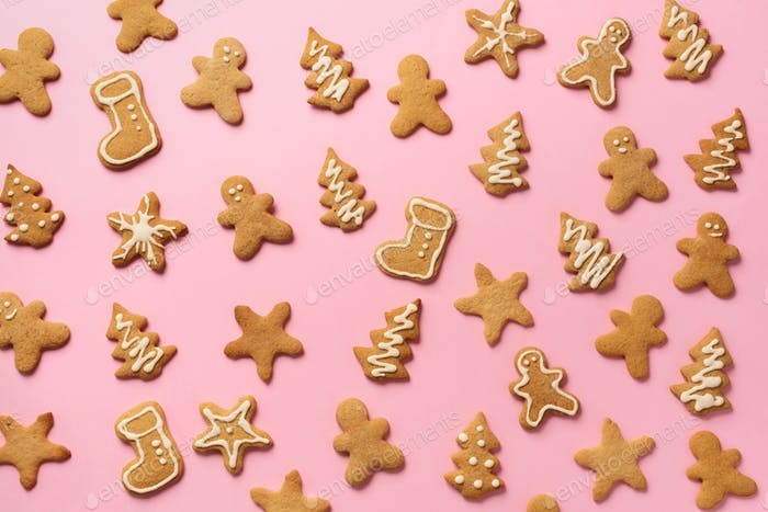 Christmas handmade cookies on pink background. Pattern of gingerbread men, snowflake, star, fir-tree