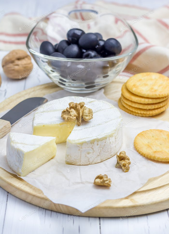 Soft brie cheese with crackers nuts and olives