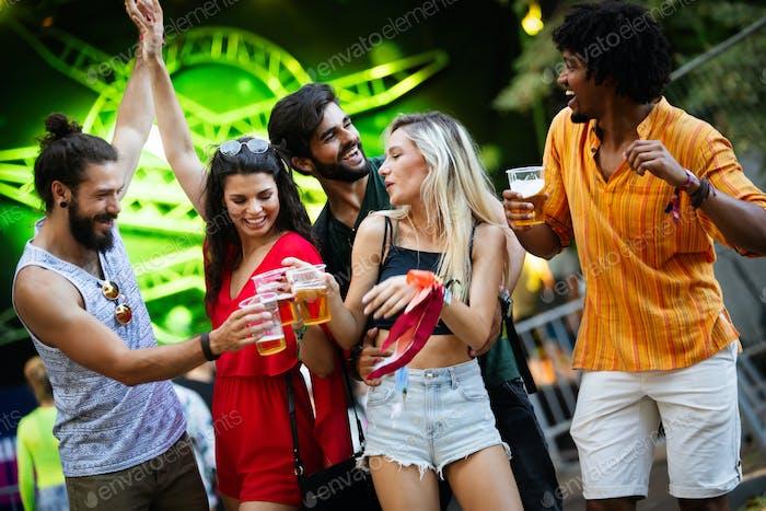 Grupo de amigos felices pasando el rato y disfrutando de bebidas, festival