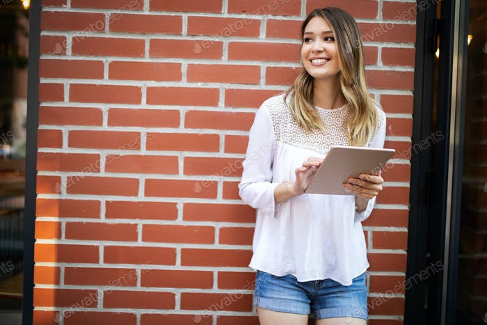 Beautiful brunette girl using tablet for work, freelance, blogging, studying, shopping