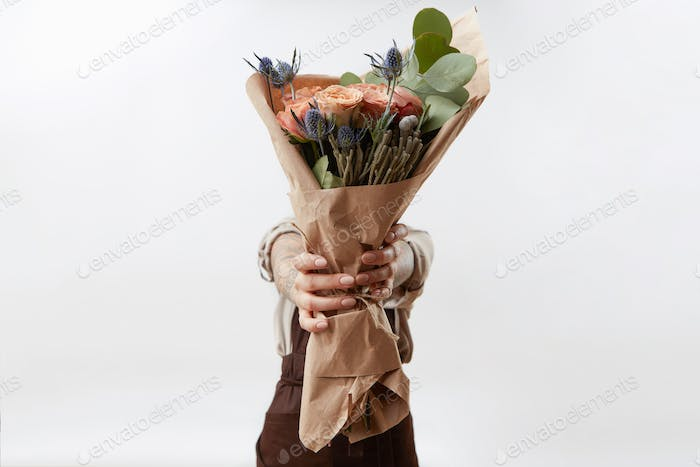 Lady's hands hold a nice bouquet from fresh fragrant flowers living coral colored roses on a