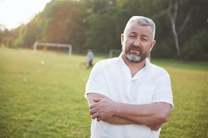 An elderly man smiles and is happy in nature