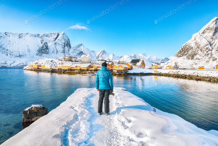 Tourist admire the view of the Sakrisoy village and snowy mountaines on background.