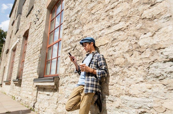 Hombre con smartphone bebiendo café en la calle de la Ciudad