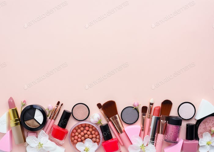 Makeup brush and decorative cosmetics with apple blossom on a pa