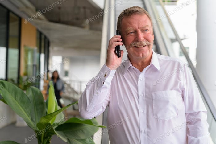 Happy senior businessman thinking while talking on the phone in the city