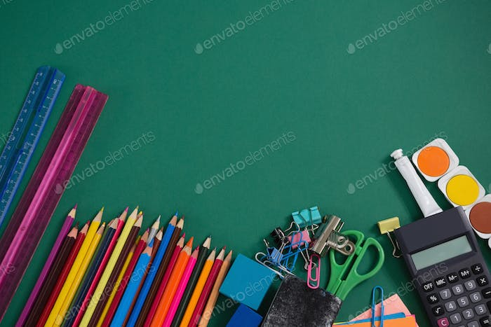 Various school supplies on green background