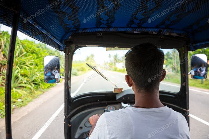 Tuk tuk driver on road of Sri Lanka, view from car