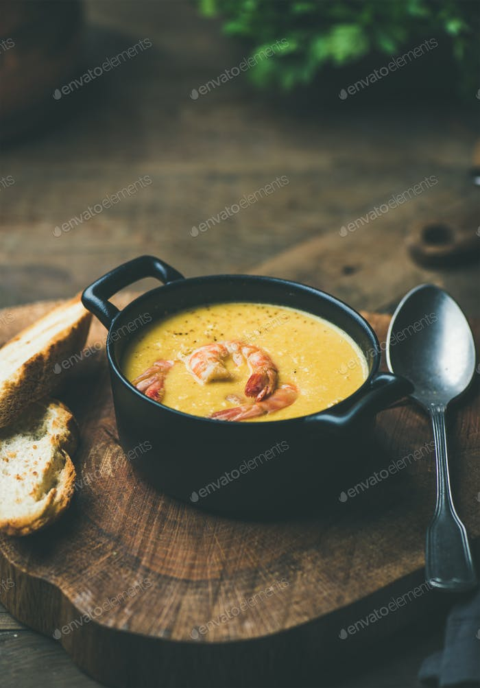 Corn creamy soup with shrimps served in pot, copy space