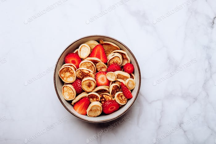 Tiny cereal pancakes and strawberries