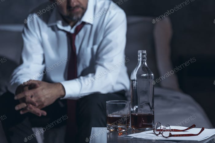 Tired man drinking alcohol