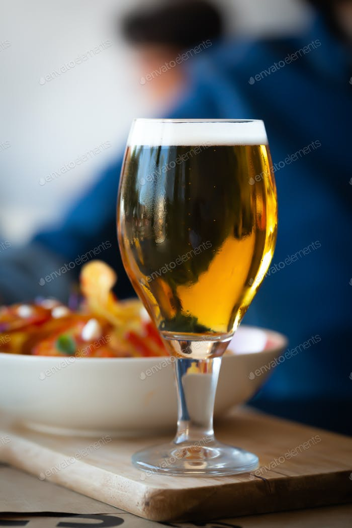 Glass of beer and chips on wooden table