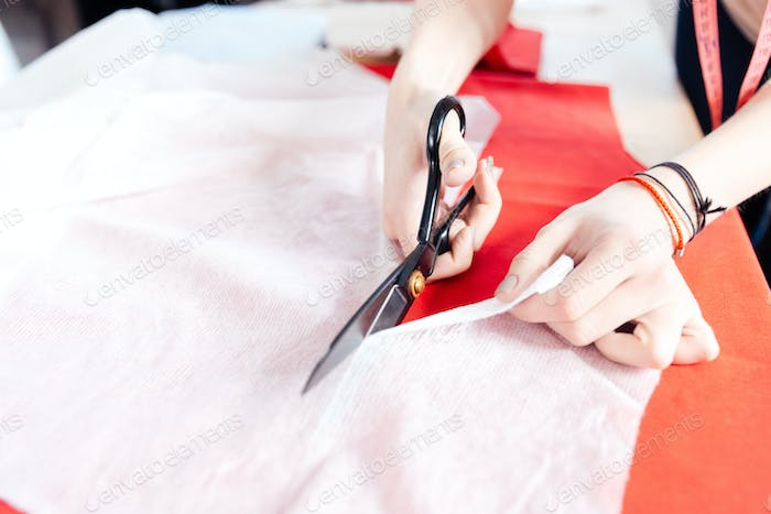Hands of woman seamstress with scissors cutting fabric
