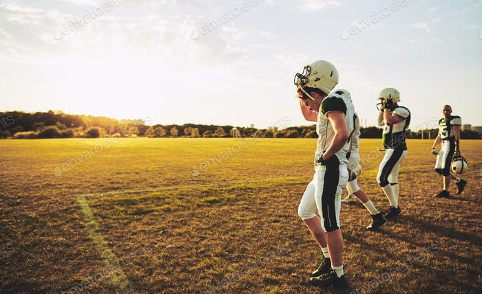 Young American football players walking off a field after practice