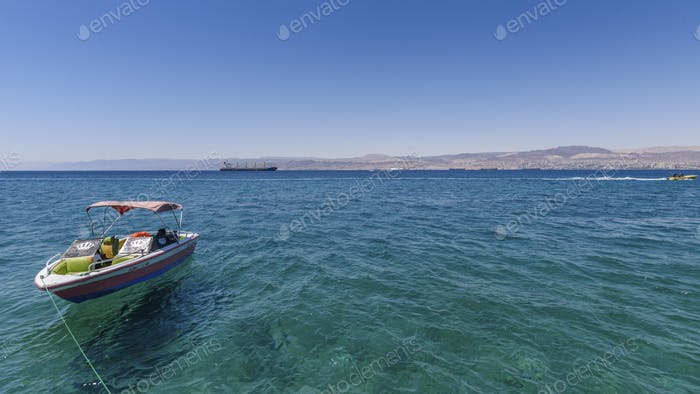 Boat moored in the Red Sea, Jordan, with coastline in the distance.