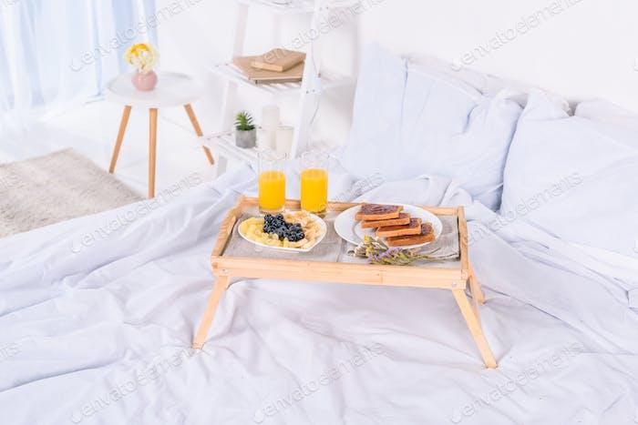 Frühstück im Bett auf Holztablett am Morgen
