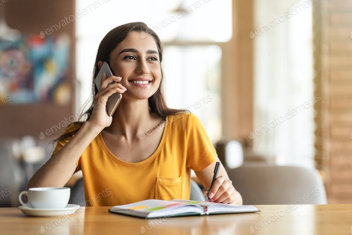 Cheerful young lady having conversation with employer on phone