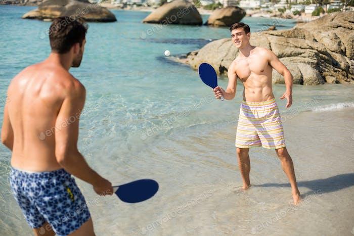 Male friends playing matkot on shore at beach